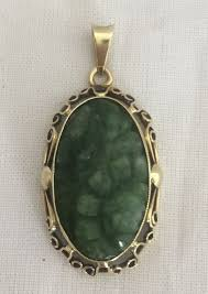 585 1000 yellow gold pendant with an oval carved jade stone with a fl