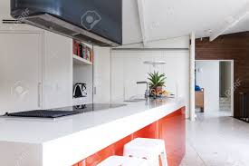 kitchen island close up. close up of modern kitchen island bench with orange accent panel color stock photo - 64885669 l