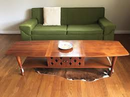 mid century modern walnut surfboard coffee table with cabinet and shelving