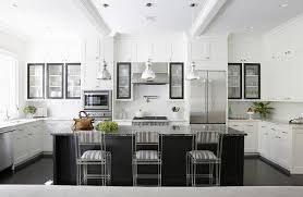 a trio of jamie young st charles pendants mercury glass pendants hangs over a black kitchen island topped with black marble lined with gray striped