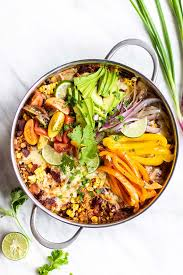 one pan mexican quinoa garnished with cheese avocado peppers and onions