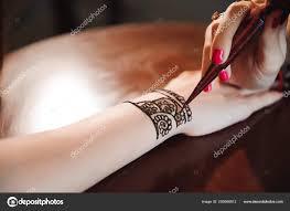 художник применяя хна татуировки на руках женщин менди