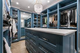 blue painted master closet with open framed cabinet doors with glass panels closet island features