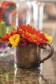 Fall flowers in silver mugs and creamers