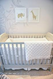 chic nursery features a gray wall accented with a tree mural lined with a gray crib pottery barn kids blythe crib placed under an elephant and giraffe art
