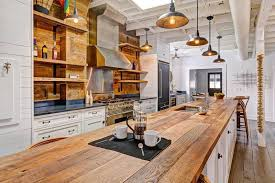 country kitchen with white cabinets and long reclaimed barn wood counter island