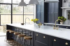 This chic vintage English kitchen features navy cabinetry and brass hardware