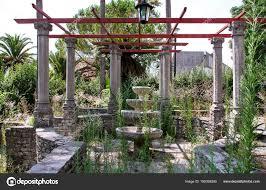 old rustic stone fountain in garden stock photo