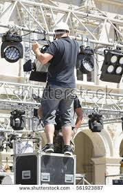 lighting technician. lighting technician iinstalling professional equipment for concert stage installation with led lights and projectors e