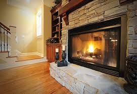 a bright fire burning in a gas insert fireplace with a stone veneer