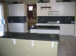 white cabinets with black granite backsplash and countertops