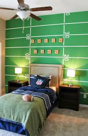 Football themed boys room. Back wall painted to look like a football field.  Easy