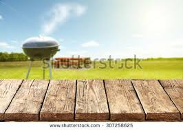 picnic table background. blurred background of green grass and blue sky grill with table place space for picnic c