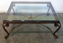 classic square glass top coffee table with ornate iron legs on grey concrete floor