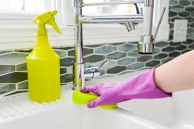 house cleaning guide to a clean home angie s list hand scrubbing white sink yellow sponge housecleaning