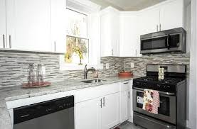 small kitchen with white cabinets and glass mosaic tile backsplash