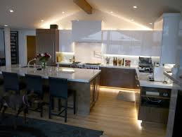 white acrylic upper cabinets walnut lower cabinets with toe kick lighting marble countertops and backsplash marble island with seating and exposed beams
