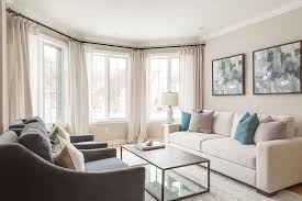 welcoming living room features bay windows dressed in cream curtains complementing cream colored walls and a cream modern sofa topped with blue and gray