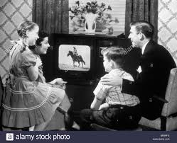 family watching tv 1950s. 1950s family of four watching black and white television program a cowboy riding horse family watching tv h