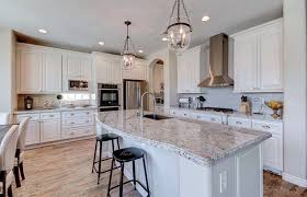 kitchen with moon white granite counters and white cabinets