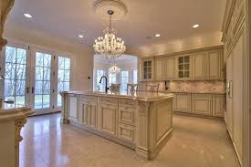 traditional kitchen with cream cabinets chandelier crema marfil marble counter and large island
