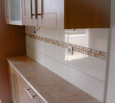 kitchen backsplash made with big white tiles and insertion of colorful glass mosaic