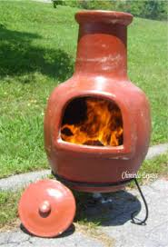 orange clay chiminea outdoor fireplace with black iron stand for patio furniture ideas