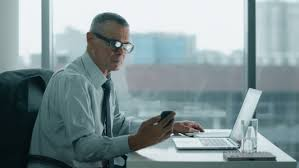 Modern office look Interior Elderly Businessman Look At Phone And Working With Computer In Modern Office stock Footage Elderly Businessman Look At Phone And Working With Computer In