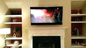 hanging tv over fireplace hanging over fireplace mounted mount too high ideas