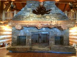 massive stone fireplace and wood mantel made out of western red cedar by pioneer log homes