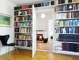 gorgeous bookshelf wall with simple door and black chair on wood floor under picture plus nice