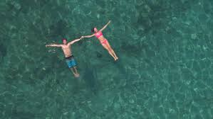 AERIAL, DISTANCING: Happy and loving girlfriend and boyfriend holding  hands, relaxing and floating