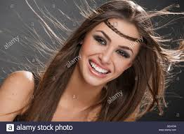 portrait of beautiful happy smiling woman with ing brown long silky hair make up
