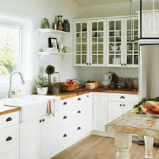 white shaker cabinets butcher block. white farmhouse sink, butcher block counters, cabinets with antique bronze hardware and open shelves, make for a classic cottage kitchen. shaker