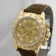 this rolex daytona is 18k yellow gold on a custom brown ostrich strap with cream colored stitching it has a factory champagne diamond dial with black