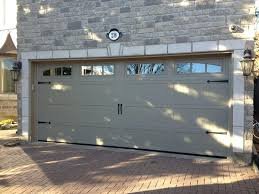 wrought iron decorative garage door hardware carriage door in sandstone with arched windows and wrought iron