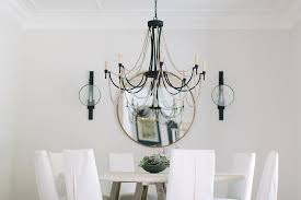 iron and gray wood beaded chandelier over round wood table