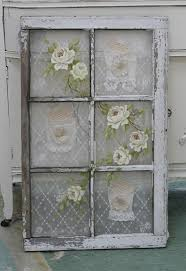 old window with vintage lace behind the panes and roses painted on the glass