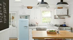 white refrigerator in kitchen. walls, cabinets, and floors are painted white to bring in as much light refrigerator kitchen o