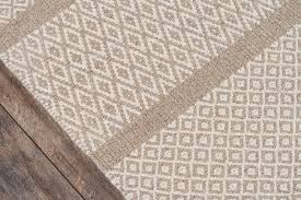 the neutral tones of this traditional area rug collection feel rustic yet refined earthy shades of natural beige brown and grey form subtle striations
