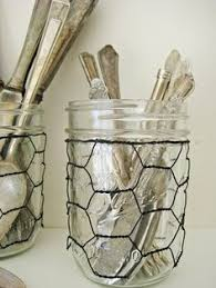 chicken wire wrapped around mason jar hang from the wagon wheel with a few jewels alternating length wagon wheel mason jar