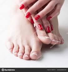 手と足を持つモデル少女のフランス語マニキュア ペディキュアと赤い爪