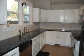 unfinished white oak kitchen cabinets with black countertops and grey wall