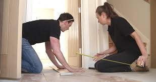 Man And Woman Laying Laminate Wood Panel Flooring In A House