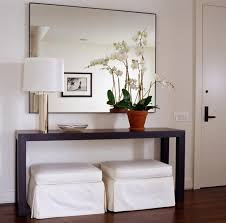 modern entryway furniture inspiring ideas white. elegant foyer slipcovered white ottomans and modern wood console table with chrome lamp large wall mirror paint color in entry entryway furniture inspiring ideas o