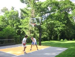 joe deshayes and his son enjoy some family time on a backyard basketball court built by