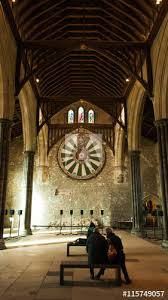 people contemplating king arthur round table in winchester great hall uk