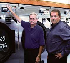 owner john craig and tom jessen right of bds laundry systems demonstrate the benefits