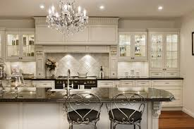 bright kitchen interior feat antique white kitchen cabinets paint also paired with long island using grey marble countertop under crystal chandelier
