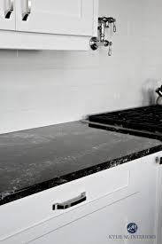 cambria ellesmere black quartz countertop white kitchen cabinets and off white light gray subway tile backsplash kylie m interiors decorating and design